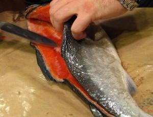 ножом чистит рыбу