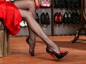 девушка в красном примеряет туфли