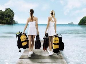 две девушки в коротких платьицах, тащат акваланги
