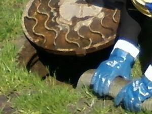 ассенизатор в синих перчатках чистит канализационный колодец