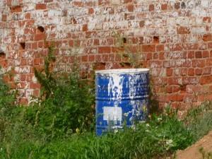бак из под краски у стены из красного кирпича